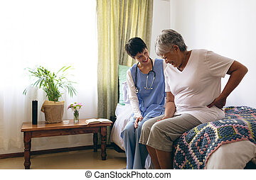 Female doctor and senior female patient interacting - Side ...