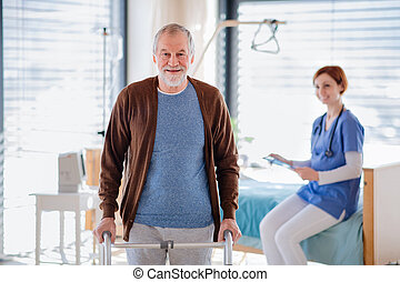 Female doctor and senior patient with walking frame in hospital.