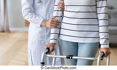 Female doctor assist senior patient with walking frame
