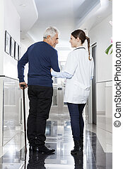 Female Doctor Assisting Man To Walk In Rehab Center