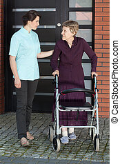 Female doctor assisting old woman with walker