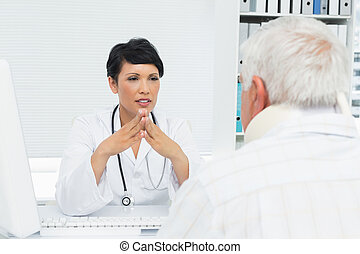 Female doctor attentively listening to senior patient -...
