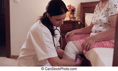 Female doctor bandages senior woman knee at home - Female...