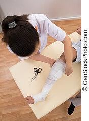 Female Doctor Bandaging Patient's Leg