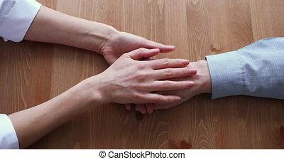 Female doctor caregiver stroking wrinkled hand of old man...