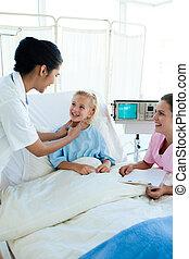 Female doctor checking blond girl\'s throat