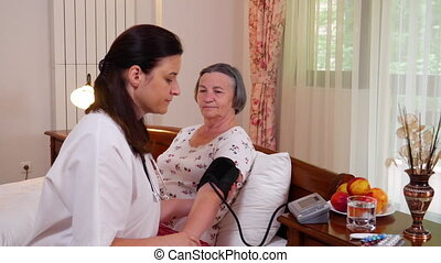 Female doctor checking blood pressure to senior woman at...