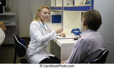Female doctor checking senoir man's temperature - Medical...