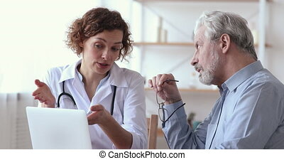 Female doctor consulting 60 years old patient at medical checkup visit. Serious physician giving advice to senior adult man client, prescribing treatment in hospital. Elder people healthcare concept