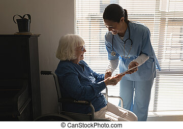 Female doctor discussing medical report with disable senior woman on digital tablet