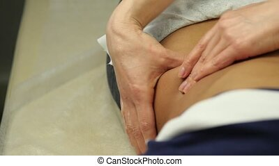 female doctor does a abdominal massage to patient. Anticellulite massage in clinic. slow motion