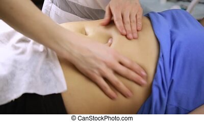 female doctor does a abdominal massage to patient