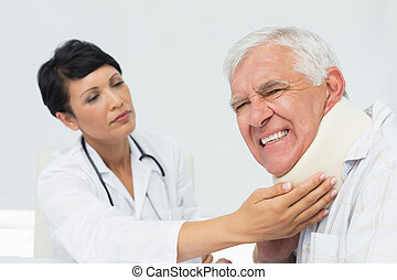 Female doctor examining a senior patients neck - Close-up of...
