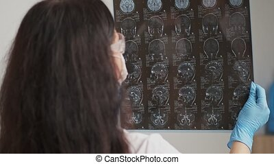 Female doctor examining an MRI image of a patient.