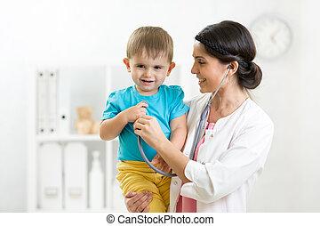 Female doctor examining child boy with stethoscope