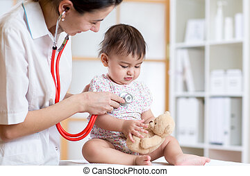 female doctor examining child toddler with stethoscope