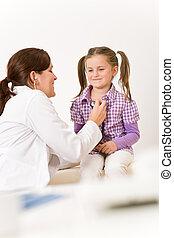 Female doctor examining child with stethoscope