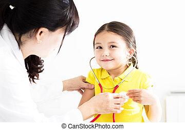 female Doctor examining  little girl by stethoscope