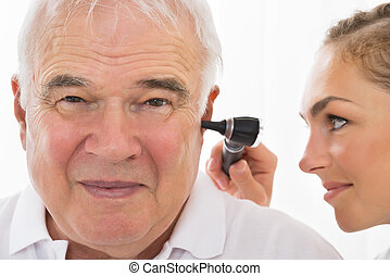 Female Doctor Examining Patient's Ear