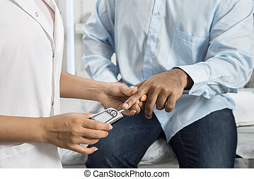 Female Doctor Examining Patient's Sugar Level With ...