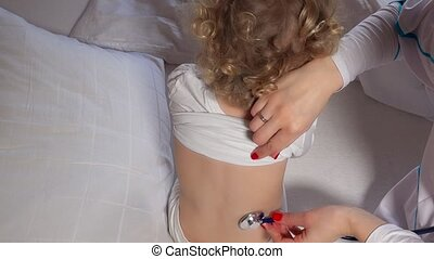 Female doctor examining toddler girl with stethoscope in bed