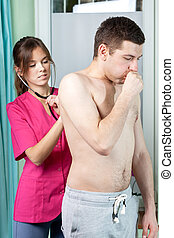 Female doctor examining young man