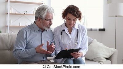 Female doctor explaining prescription recipe talking to homecare old male patient. Senior grandfather client and his attending physician read medical insurance for aged people at medicare home visit.