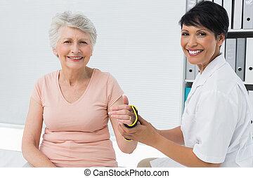 Female doctor fixing wrist brace on senior patients hand in...