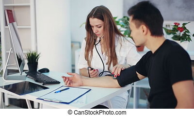 Female doctor girl measures blood pressure to a man