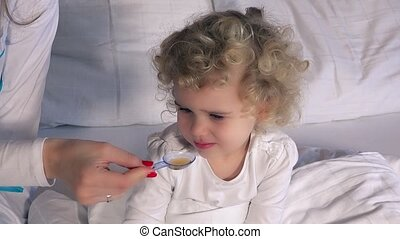 Female doctor giving a spoon of syrup to little sick girl sitting in bed
