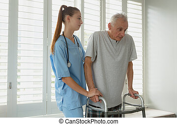 Female doctor helping active senior man to walk with walker