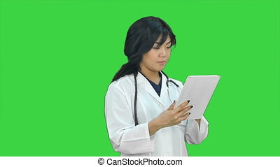 Female doctor holding digital tablet presenting project looking at camera on a Green Screen, Chroma Key