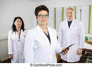 Female Doctor Holding Digital Tablet While Standing With Colleag