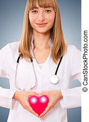 Female doctor holding  heart.