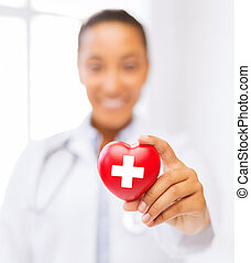 female doctor holding heart with red cross symbol