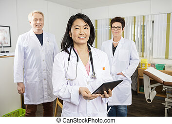 Female Doctor Holding Tablet Computer While Standing With Collea