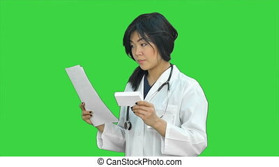 Female doctor holding up a box of tablets, smiling and presenting it on a Green Screen, Chroma Key