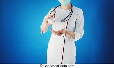 Female doctor in a white coat and mask with a pill in her hands.