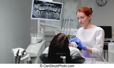 Female doctor in blue gloves and a white coat approaches to the chair of the patient and using x-ray and instruments the dentist inspects the teeth in the oral cavity. Girl patient.