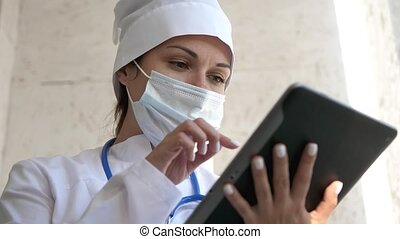 Female doctor in medical mask is using a tablet computer