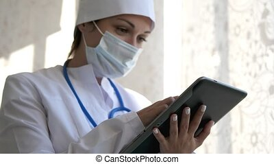 A sliding shot of a female doctor is using a tablet computer on break time, and she got good news on inbox.