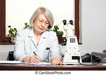 Female doctor in office writing