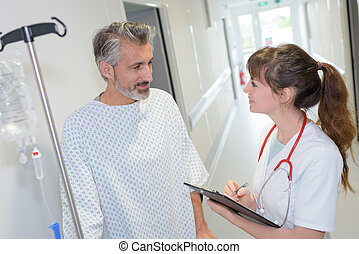 female doctor interacting with patient in hospital corridor