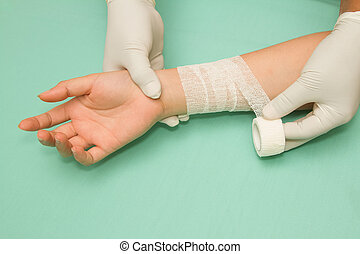 Female doctor is bandaging forearm of patient.