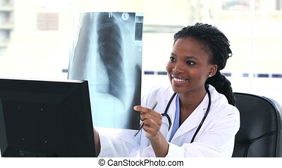 Female doctor looking at a chest X-ray while sitting at her...