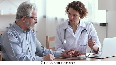 Female doctor measuring high low blood pressure of elderly male patient in hospital. Cardiologist examining old man hypertension sufferer using medical tonometer. Seniors cardiology healthcare concept