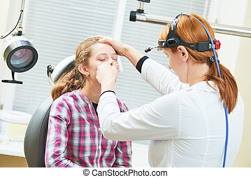 female doctor of ENT ear nose throat at work examining girl nose