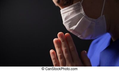 female doctor or nurse in face mask praying - health, ...
