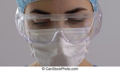 health, medicine and pandemic concept - sad young female doctor or nurse wearing goggle, hat and face protective mask for protection from virus disease over grey background