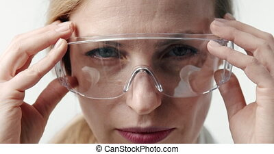 Female doctor putting on protective eyewear - Female doctor ...
